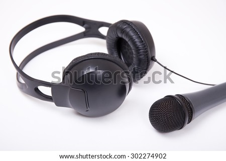 music concept - close up of microphone and headphones over white background