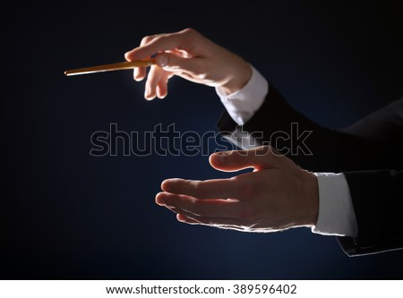 Music conductor directing with baton on black lightened background, close up - stock photo
