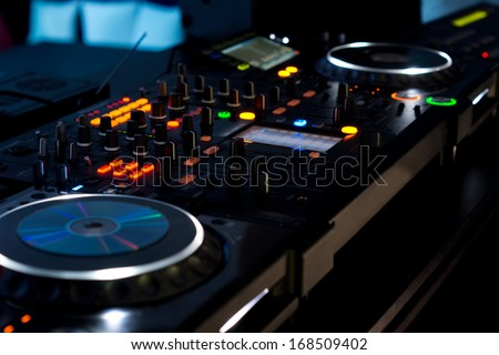 Music deck at a disco with two turntables and multiple switches and sliders illuminated with colourful lights at night in a discotheque - stock photo
