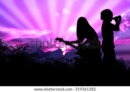 Music for the Earth Rocker and Guitarist are Singing and Playing Rock Music Against the Background of Purple Sky - stock photo