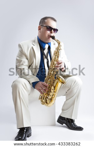 Music Ideas and Concepts. Handsome and Caucasian Music Player Posing In Sunglasses With Saxophone Against White Background. Vertical Image Orientation - stock photo