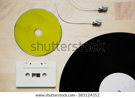 music in green cd cassette tape vinyl disk and earphone on wood background