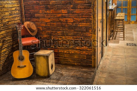 Music instruments on wooden stage in pub - stock photo