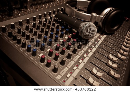 Music instruments or dj concept.the microphone and headphones on sound mixer background. - stock photo