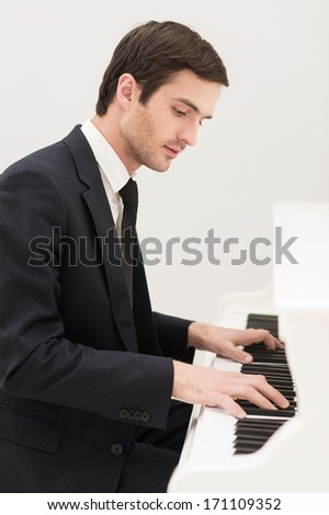 Music is everything. Confident young man in formalwear playing piano - stock photo