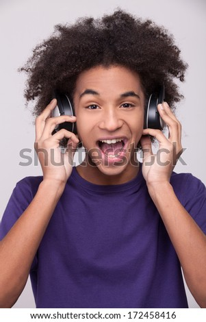 Music is my life! Cheerful African teenager in headphones listening to the music and expressing positivity while standing isolated on grey background - stock photo