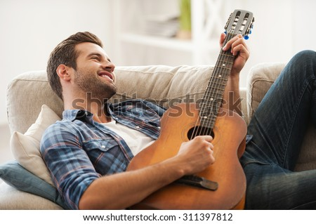 Music is my life. Happy young man playing the guitar while lying on sofa - stock photo