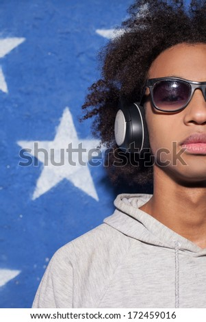 Music lover. Cropped image of confident young African man in headphones standing against American flag and listening to the music - stock photo
