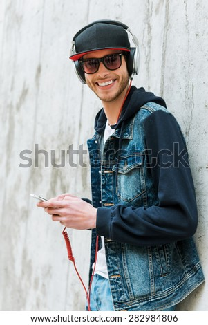 Music lover. Happy young man in headphones holding mobile phone while leaning at the concrete wall  - stock photo