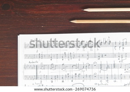 Music notes and two pencils on table