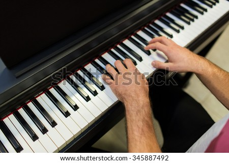 music, people, art, musical instruments and entertainment concept - close up of male hands playing piano