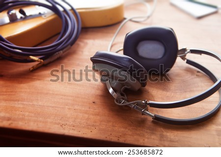 Music Recording scene. Professional grade headphones on a rustic or bare wooden table, with by-the-window type warm light. An electric guitar, memo pad , in the background. Shallow depth of field. - stock photo