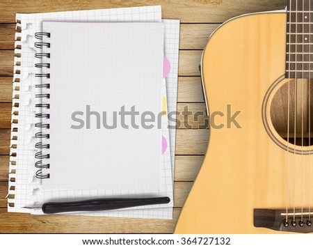 Music recording scene with guitar, notebook and music sheets on wooden table - stock photo
