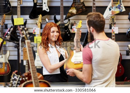 music, sale, people, musical instruments and entertainment concept - female assistant showing electric guitar to customer at music store