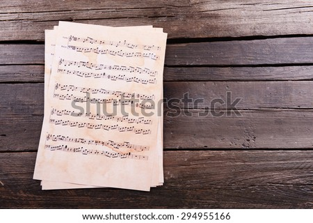 Music sheets on wooden background - stock photo