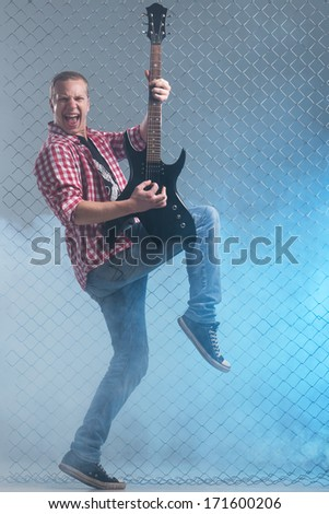 Music, sound. Musician with a guitar on fence background - stock photo