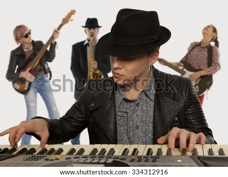 Musical band. Man in the hat playing on a synthesizer