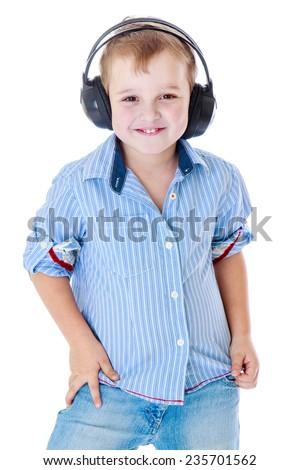 Musical development, aesthetic education, the joy of communication concept - Cheerful little boy in a blue shirt is listening to music in big black headphones. - stock photo