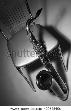 musical instrument saxophone and chair against dark background - stock photo