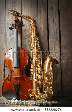 Musical instruments: saxophone, violin and flute with notes on wooden background - stock photo
