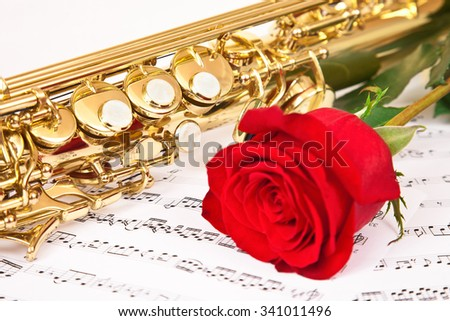 Musical notes and saxophone with red  rose - stock photo