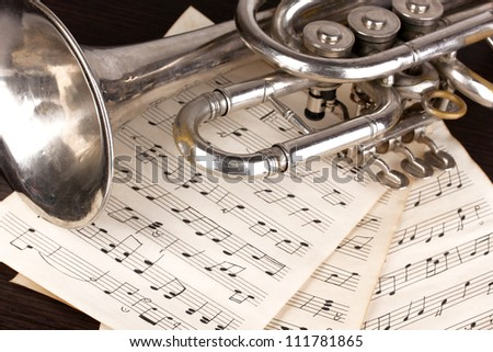 Musical notes and trumpet on wooden table
