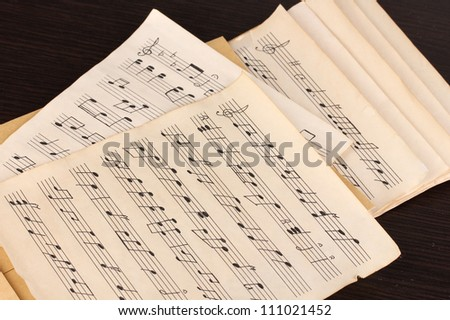 Musical notes on wooden table - stock photo