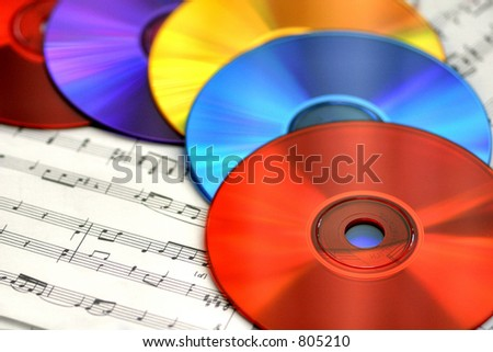Musical Rainbow:A colorful array of CDs on sheet music. - stock photo