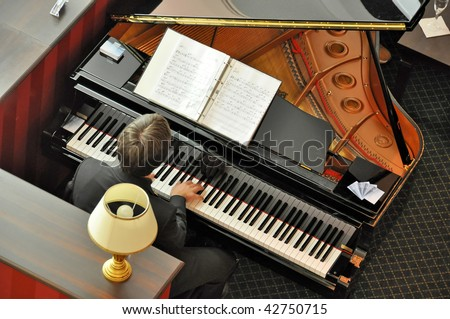 Musician at piano in lounge - stock photo