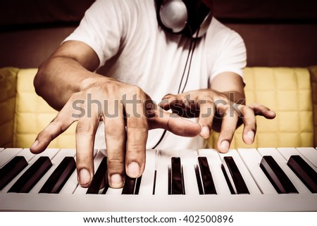musician hands playing white piano + art filter for music background - stock photo