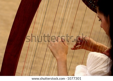 Musician is playing harp - stock photo