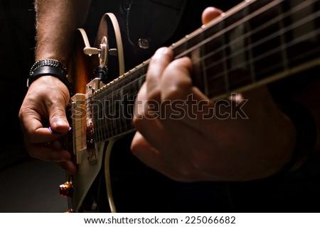 musician man playing guitar, close-up shot, dark background - stock photo