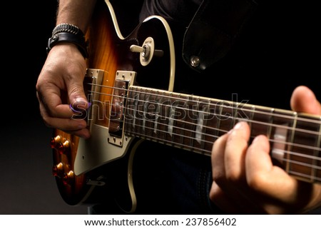 musician men playing on guitar, close-up shot, dark background - stock photo