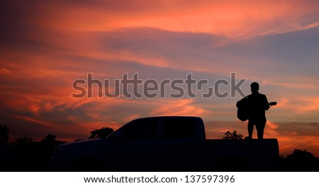 musician on the car sunset beautiful sky for design - stock photo