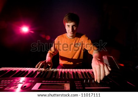 musician play on the keyboard synthesizer - stock photo