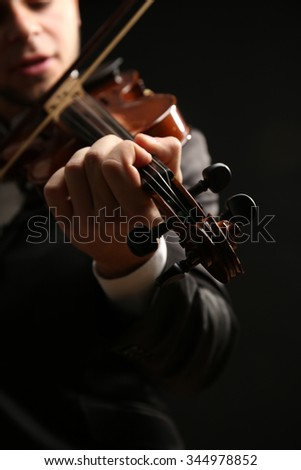 Musician play violin on black background, close up