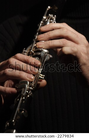 musician playing a clarinet isolated against black background - stock photo
