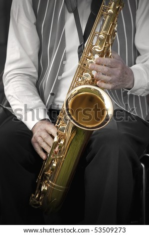 musician playing his instrument in a jazz band - color only on the sax - stock photo