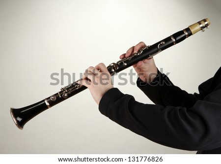 Musician playing on clarinet on grey background