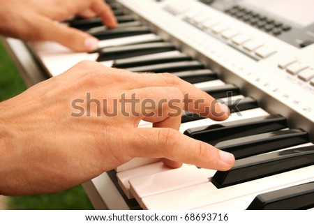 Musician playing on keyboards. - stock photo