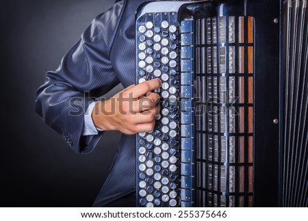Musician playing the accordion against a black background - stock photo