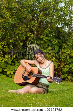 Musician playing the guitar and singing in the park - stock photo