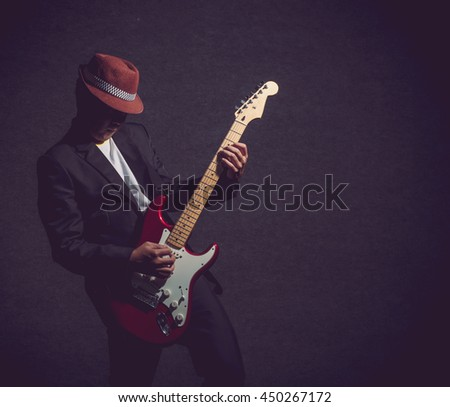 Musician playing the guitar on dark background,music concept