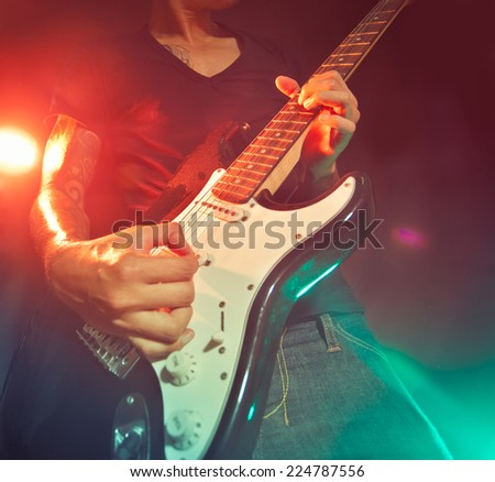 Musician playing the guitar on the stage - stock photo