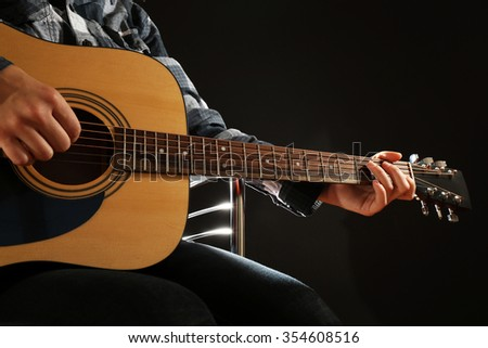 Musician plays guitar on black background, close up