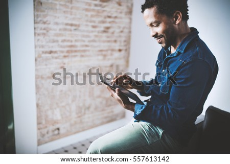 Musing bearded African American freelancer touching display of digital tablet while working in new project at home.Black businessman looking for information on Internet.Blurred,color filter