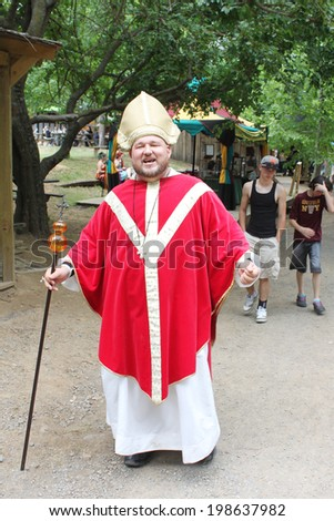MUSKOGEE, OK - MAY 24: A man dressed as a cardinal poses for a picture at the Oklahoma 19th annual Renaissance Festival on May 24, 2014 at the Castle of Muskogee in Muskogee, OK.  - stock photo