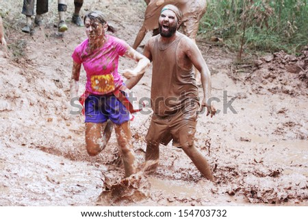 MUSKOGEE, OK - SEPT. 14 : Actors portraying zombies wait for runners to cross their mud pit  during the Castle Zombie Run at the Castle of Muskogee in Muskogee, OK on September 14 , 2013. - stock photo