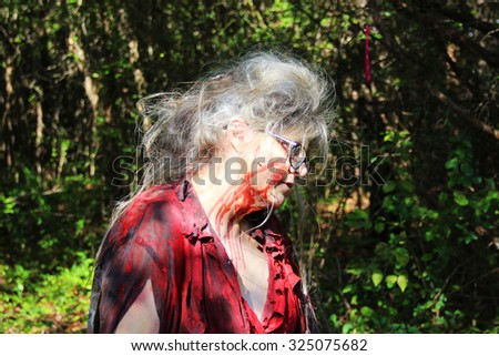 MUSKOGEE, OK - Sept. 12: An old woman with bloody face waits to scare athletes who try to avoid zombies during the Castle Zombie Run at the Castle of Muskogee in Muskogee, OK on September 12, 2015.   - stock photo