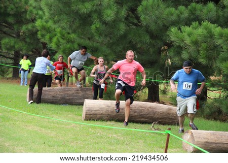 MUSKOGEE, OK - Sept. 13: Athletes jump over obstacles during the Castle Zombie Run at the Castle of Muskogee in Muskogee, OK on September 13, 2014.  - stock photo